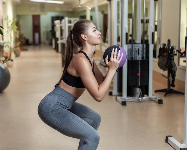 Conceito de treinamento funcional. young cabe mulher sportswear agacha-se com bola medicinal nas mãos na academia