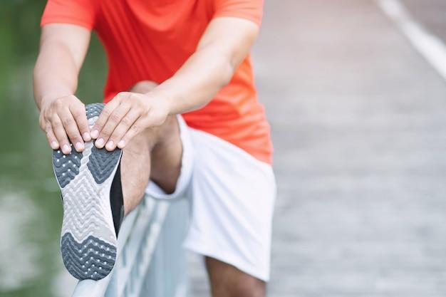 Conceito de treino e bem-estar do homem: o corredor asiático aquece o corpo antes de começar a correr na estrada do parque.
