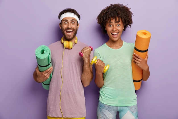 Conceito de treino, fitness e esporte. casal alegre de raça mista tem treino, levanta os braços com halteres, segura esteiras, tem treino no ginásio. a família desportiva pratica desporto junta. estilo de vida saudável