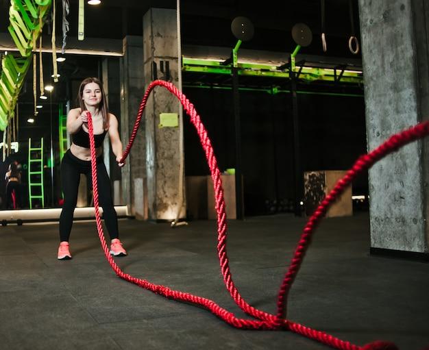 Conceito de treino. treino poderoso jovem atraente com cordas no ginásio.