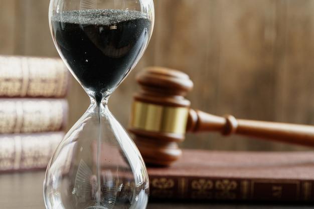 Conceito de tribunal. ampulheta e juiz martelo na mesa close-up