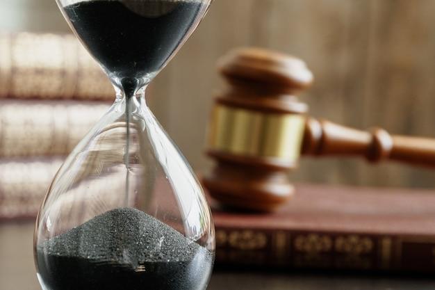 Conceito de tribunal. ampulheta e martelo de juiz na mesa