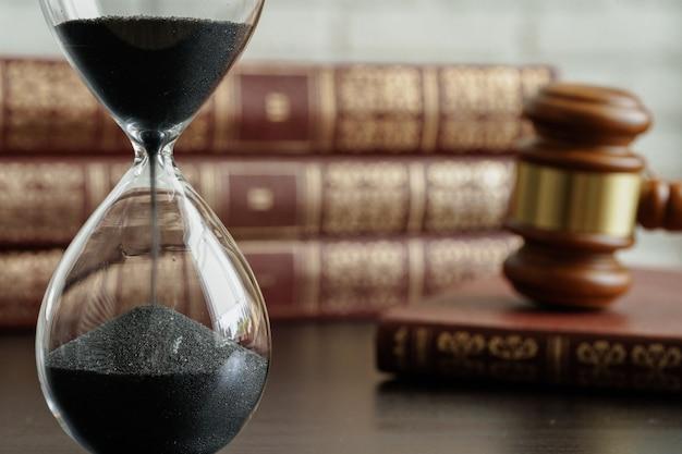Conceito de tribunal. ampulheta e martelo do juiz na mesa fecham