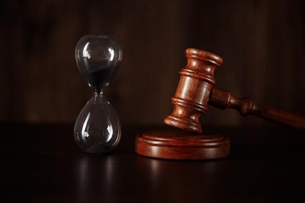 Conceito de tribunal. ampulheta e o martelo do juiz na mesa fecham.