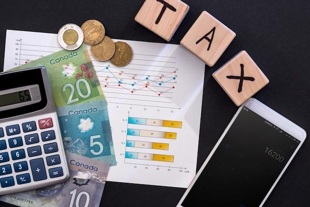 Conceito de tributação com dólar canadense, gráfico de negócios e telefone