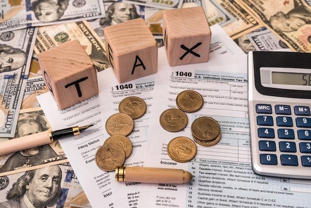 Conceito de tributação com tijolos de madeira e moeda de dólar