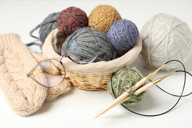Conceito de tricô com bolas de lã em fundo branco.