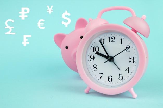 Conceito de troca de moeda global cofrinho rosa em forma de porco com moedas do mundo de holograma digital holograma sobre fundo azul. economize o conceito de tempo.