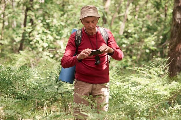 Conceito de turismo, caminhadas, floresta e tecnologia. idoso viajante masculino caucasiano usa telefone de mão, fazendo foto ou vídeo de bom humor