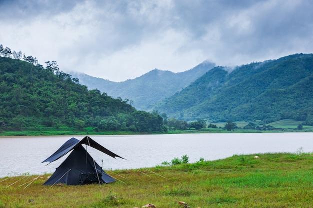 Conceito de turismo de natureza com tenda à beira do lago
