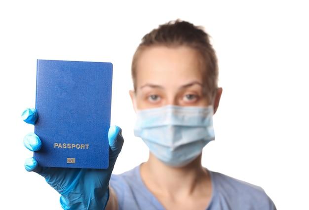 Conceito de turismo durante a pandemia covid-19. passaporte de imunidade. mulher com máscara médica segurando um passaporte isolado no branco