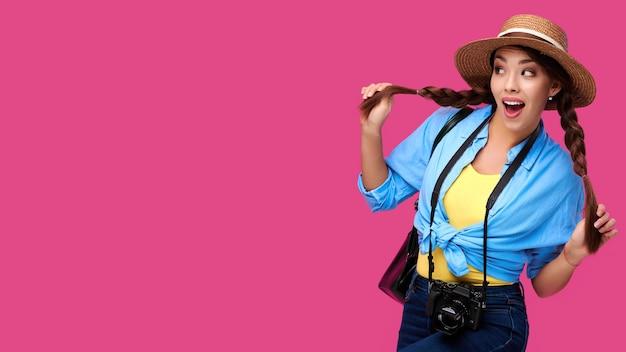 Conceito de turismo. turista excitada jovem caucasiana com câmera fotográfica, isolada no fundo rosa. hipster de aluna em roupas casuais e chapéu de palha