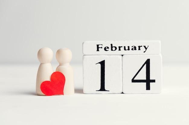 Conceito de um casal apaixonado ao lado do calendário de 14 de fevereiro do dia dos namorados.