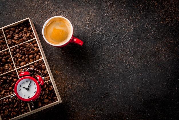 Conceito de um começo alegre e bom para o dia, café da manhã. fundo enferrujado escuro com grãos de café, um despertador e uma xícara de café. espaço de cópia da vista superior