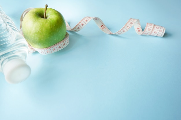 Conceito de um estilo de vida saudável. água, medidor de glicose e maçã verde sobre fundo azul