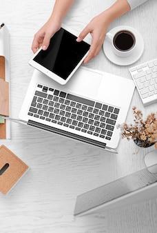 Conceito de uso de eletrônica. mulher de negócios trabalha no escritório, close-up. computador, laptop, tablet, xícara de café e outras coisas em cima da mesa. vista do topo