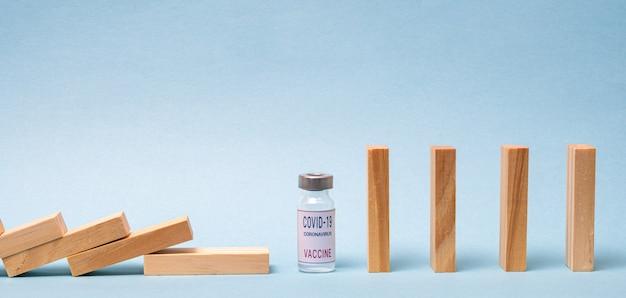 Conceito de vacina com dominó de madeira e ampola de vacina covid-19 sobre fundo azul.