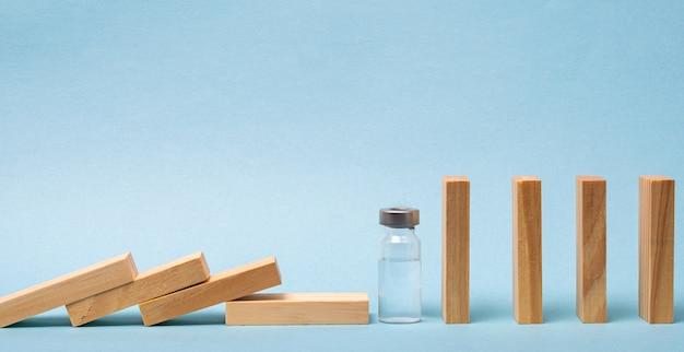 Conceito de vacina com dominó de madeira e ampola em fundo azul.