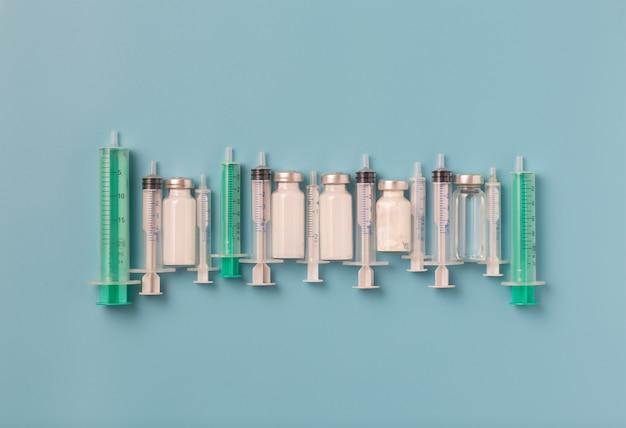 Conceito de vacinação para a pandemia de covid 19 seringas médicas, ampolas e medicamentos em um fundo azul