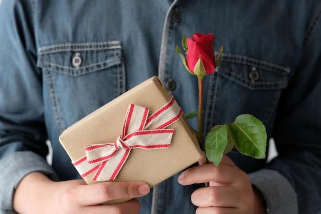 Conceito de valentim, mão de homem segurando rosa vermelha e caixa de presente