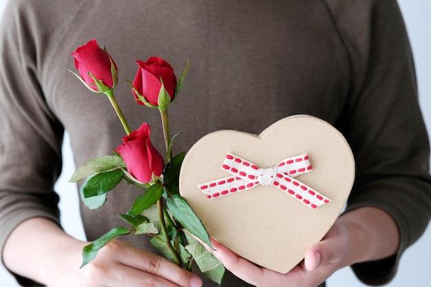 Conceito de valentim, mão de homem segurando rosas vermelhas e caixa de presente
