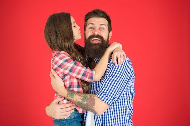 Conceito de valores familiares. laços familiares. relações amigáveis. pai moderno e sua filha. abraço doce. homem barbudo pai e filha menina bonitinha sobre fundo vermelho. comemore o dia dos pais.
