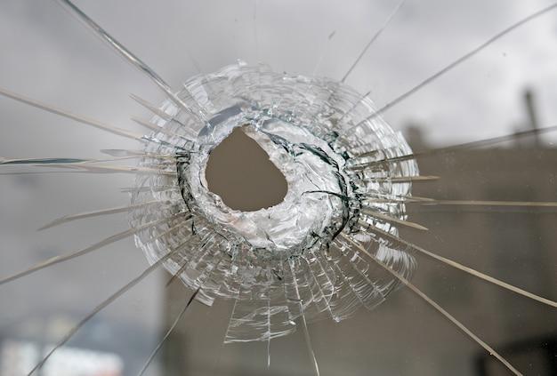 Conceito de vandalismo ou violência. vidro quebrado com furo