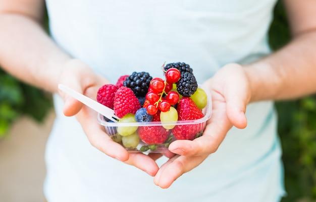 Conceito de vegetarianos, alimentos crus e dietas - close-up das mãos do homem segure frutas e bagas.