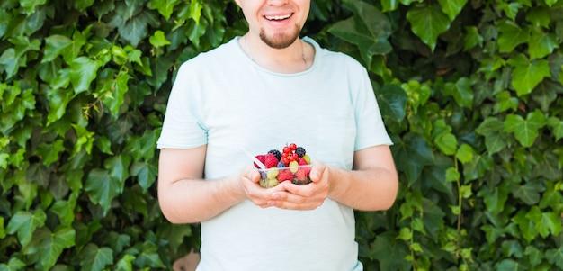 Conceito de vegetarianos, alimentos crus e dietas - close-up do homem segura frutas e bagas.