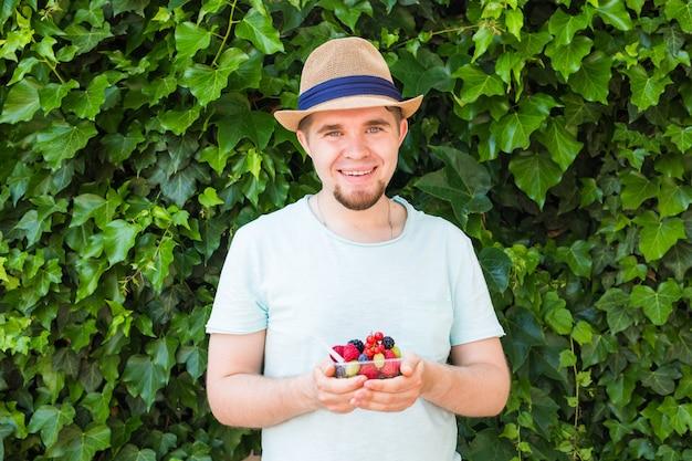 Conceito de vegetarianos, alimentos crus e dietas - homem bonito segurando frutas e bagas