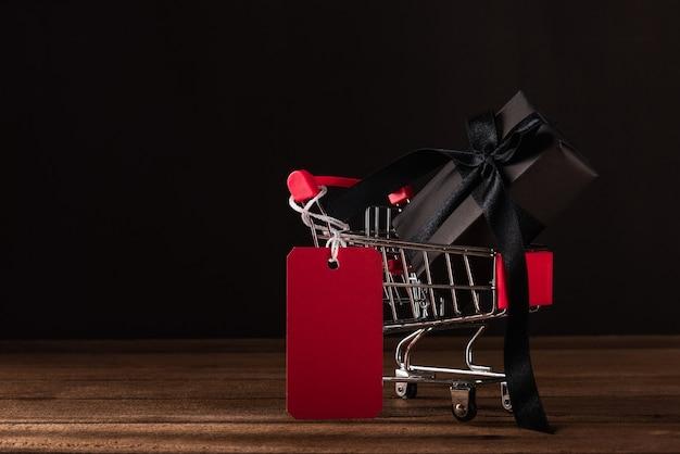 Conceito de venda black friday caixa de presente embrulhada em papel preto no carrinho de compras com etiqueta vermelha