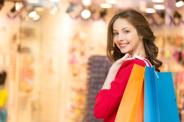 Conceito de venda, compras, turismo e pessoas felizes - linda mulher com sacolas de compras na cidade