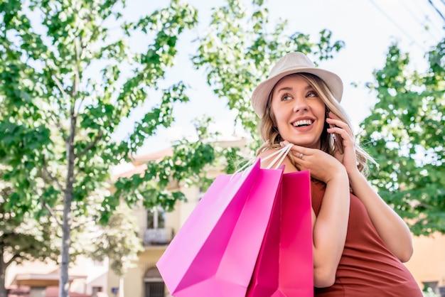 Conceito de venda, consumismo e pessoas - jovem feliz com sacolas de compras caminhando pela rua da cidade