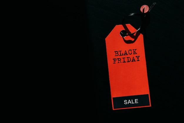 Conceito de venda de compras de sexta-feira negra. texto na etiqueta vermelha em fundo preto de madeira