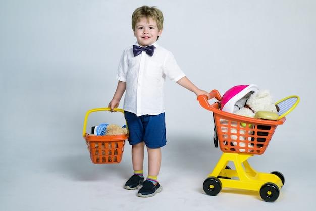Conceito de venda de desconto de compras menino alegre com carrinho de compras e cesta de criança brinca na loja