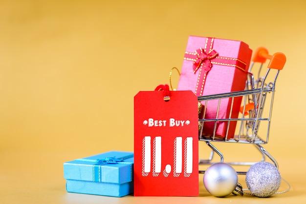 Conceito de venda de dia único chinês 11,11. mini carrinho de compras e caixa de presente com etiquetas de etiqueta.