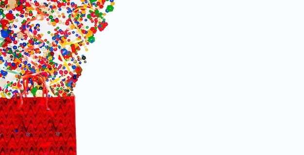 Conceito de venda de férias: saco de papel vermelho e confetes estrela em fundo preto.