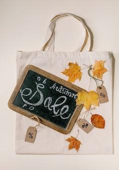 Conceito de venda de outono. lousa vintage com escritos à mão letras venda, rótulos com porcentagens, folhas de outono amarelas na sacola de compras de linho eco sobre a superfície bege. postura plana.