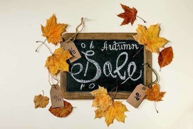 Conceito de venda de outono. lousa vintage com escritos à mão letras venda, rótulos com porcentagens, folhas de outono amarelas sobre superfície bege. postura plana.
