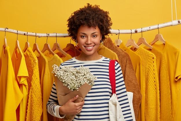 Conceito de venda de roupas. mulher afro-americana encaracolada e alegre de bom humor, segurando um lindo buquê, sorri amplamente, carrega uma sacola de compras e fica de pé contra cabides