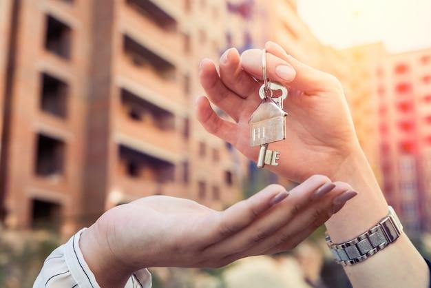 Conceito de venda entregando as chaves para o novo proprietário no fundo do plano de fundo da área residencial