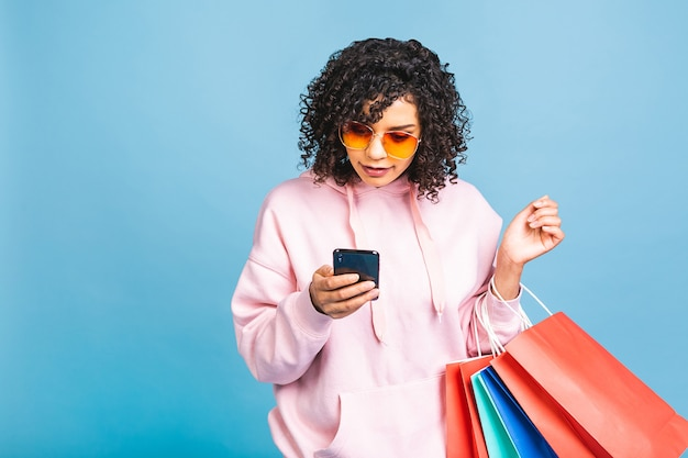 Conceito de venda! linda mulher negra afro-americana, sorrindo e segurando sacolas de compras isoladas sobre fundo azul. usando o celular.