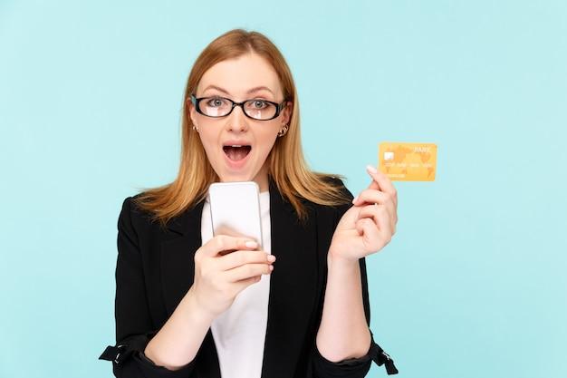 Conceito de venda. mulher segurando o cartão de crédito com o telefone e usando-o para fazer compras online.