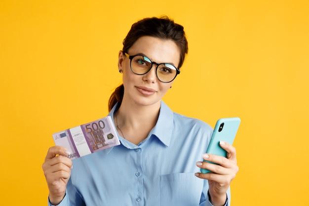 Conceito de venda online. mulher de negócios elegante com dinheiro e telefone no estúdio amarelo.
