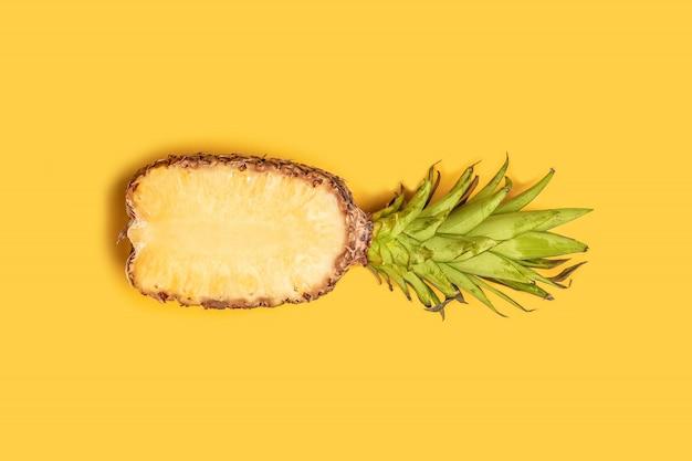 Conceito de verão. a metade fresca cortou o abacaxi no fundo amarelo.