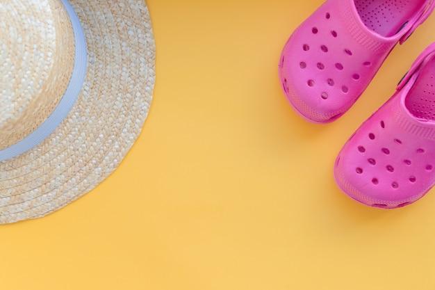 Conceito de verão com acessórios para praia. fundo de férias viagens. chinelos, sandálias, chapéu de palha sobre um fundo amarelo. itens de férias e viagens. vista superior.