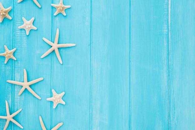 Conceito de verão com estrela do mar em um fundo azul de madeira com espaço de cópia