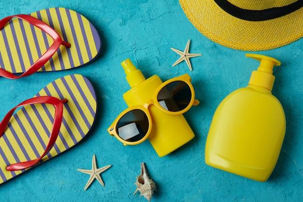 Conceito de verão com protetor solar em fundo azul texturizado isolado