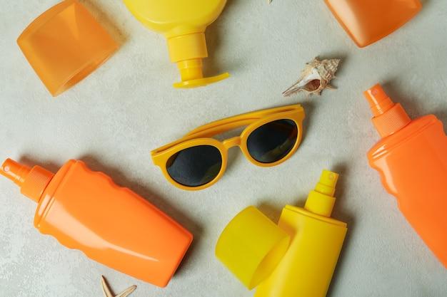 Conceito de verão com protetores solares em fundo texturizado isolado