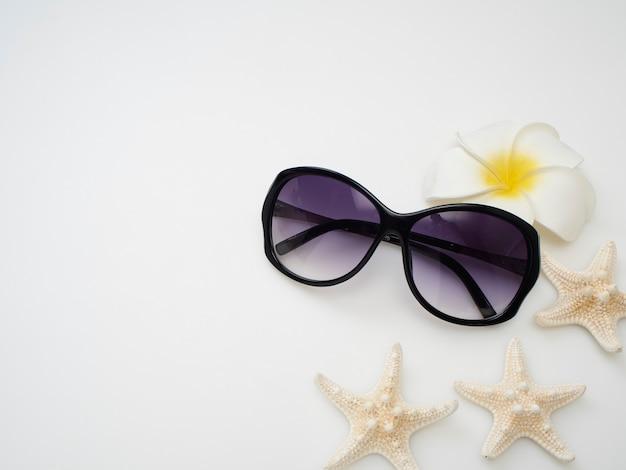 Conceito de verão. conchas, estrelas do mar, óculos escuros em um fundo branco